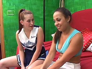 Two innocent looking cheerleaders sharing a massive dildo in the bedroom